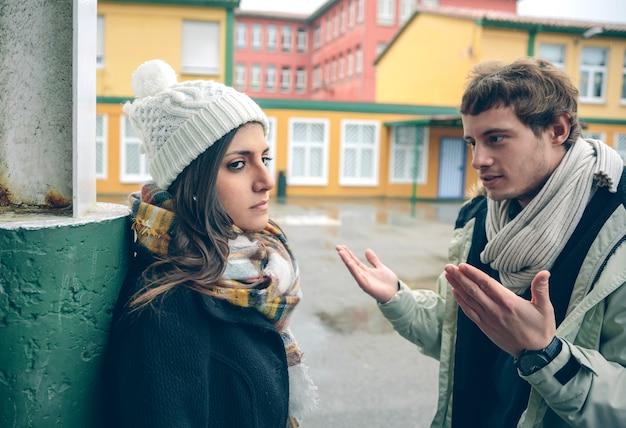 Jonge ontevreden vrouw luisteren argumenten van man tijdens een harde ruzie buitenshuis. paar relaties en problemen concept.
