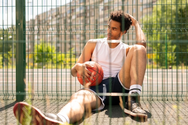 Jonge ontspannen actieve man met bal zittend door hek van basketbalveld tijdens een korte pauze