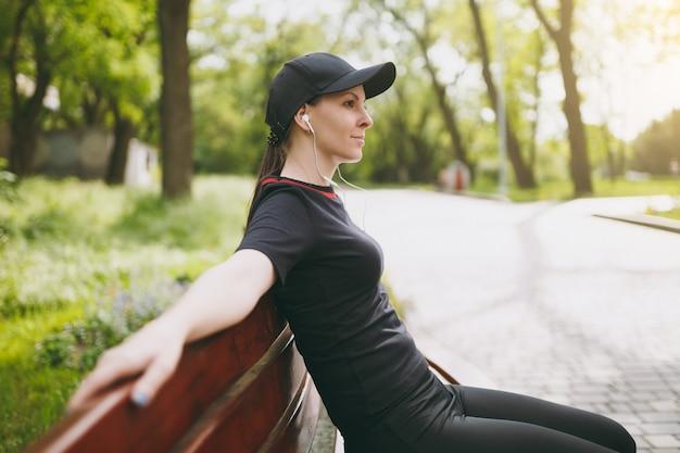 Jonge ontspannen atletische mooie brunette vrouw in zwart uniform en pet met koptelefoon rusten na training training luisteren naar muziek op bankje in stadspark buitenshuis