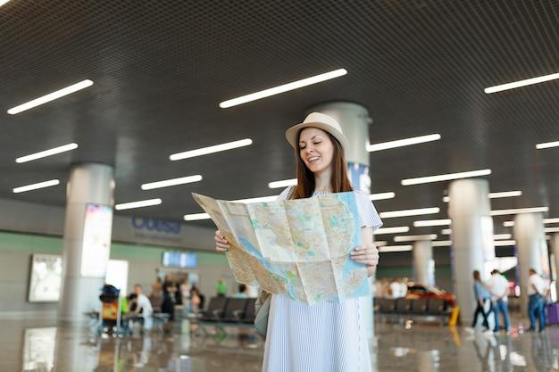 Jonge ontspannen reiziger toeristische vrouw in hoed met papieren kaart, route zoeken tijdens het wachten in de lobby hal op de internationale luchthaven