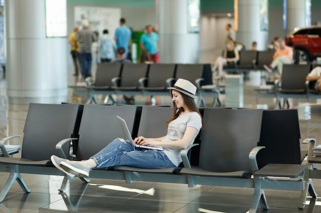 Jonge ontspannen reizigerstoeristenvrouw met hoed die aan laptop werkt terwijl ze wacht in de lobby op de internationale luchthaven
