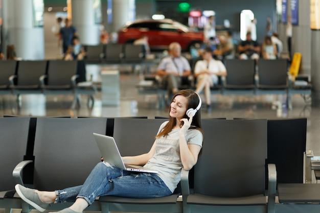 Jonge ontspannen reizigerstoeristenvrouw met koptelefoon die muziek luistert die op laptop werkt, wacht in de lobby op de internationale luchthaven