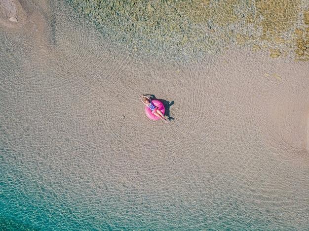Jonge ontspannen vrouw in een zwembroek zwemt in het water op een opblaasbare flamingo en zonnebaadt. uitzicht van boven.