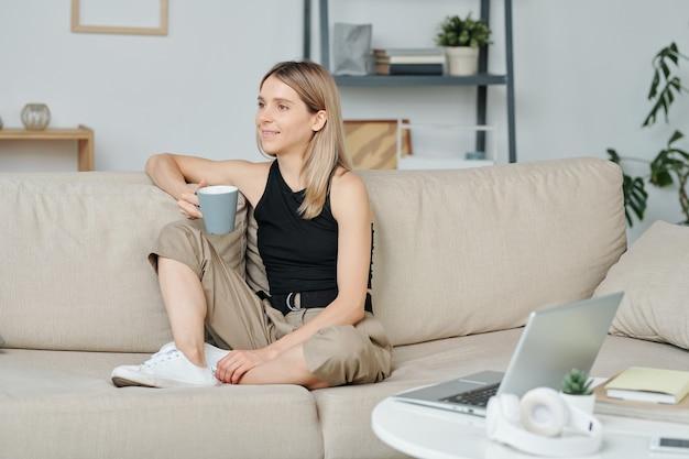 Jonge ontspannen vrouw met koffie zittend op een zachte comfortabele bank in de woonkamer, drinken en dagdromen terwijl ze thuis tijd doorbrengt