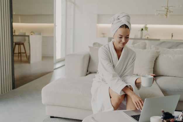 Jonge ontspannen vrouw vrouwelijke freelancer in witte badjas en handdoek op hoofd koffie of thee drinken en op afstand werken op laptopcomputer, rustend op de bank in de moderne woonkamer na het douchen
