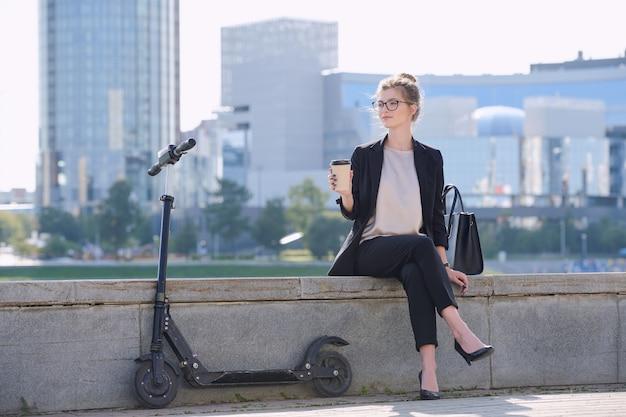 Jonge ontspannen zakenvrouw met een glas koffie aan de rivier met een elektrische scooter in de buurt tegen een groep moderne architectuur
