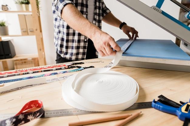 Jonge ontwerper die nieuwe apparatuur gebruikt voor het afdrukken van ornamenten op handgemaakte halsbanden voor huisdieren terwijl hij bij de tafel staat