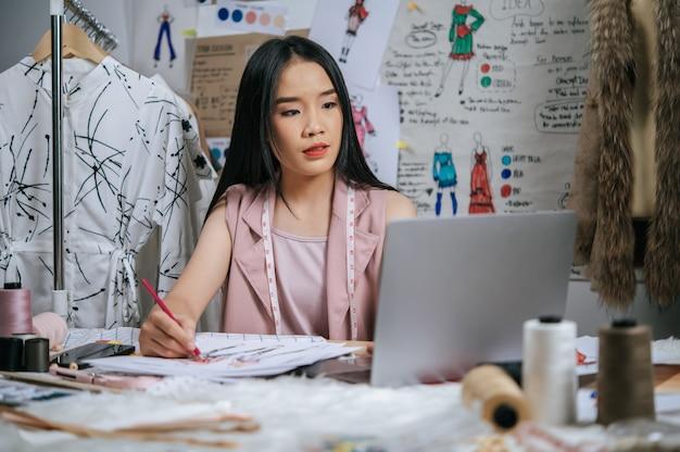 Jonge ontwerper gebruikt laptopcomputer om idee te zoeken terwijl hij de modekleding op papier schetst