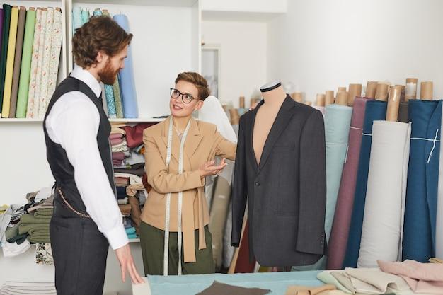 Jonge ontwerper wijzend op jas die op etalagepop hangt en praat met haar cliënt in de werkplaats