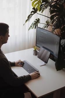 Jonge ontwikkelaar werkt thuis met groot scherm en tablet thuiskantoorinrichting met planten