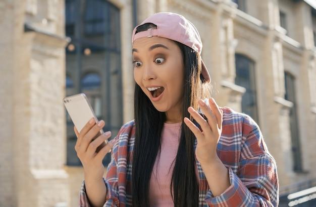 Jonge opgewonden aziatische vrouw met smartphone