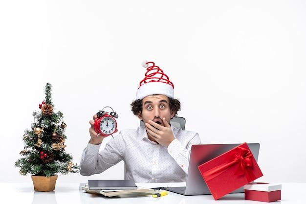 Jonge opgewonden geschokte bedrijfspersoon met kerstman hoed en klok tonen werken alleen zittend in het kantoor op witte achtergrond