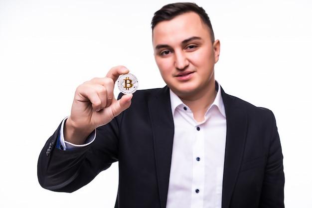 Jonge opgewonden man op wit houdt bitcoin munt in zijn handen