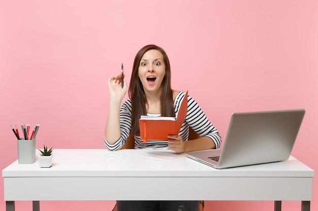 Jonge opgewonden vrouw denkt met een nieuw idee, dacht met potlood, notebook te zitten en te werken aan een wit bureau met pc-laptop geïsoleerd op een pastelroze achtergrond. prestatie zakelijke carrière. ruimte kopiëren.