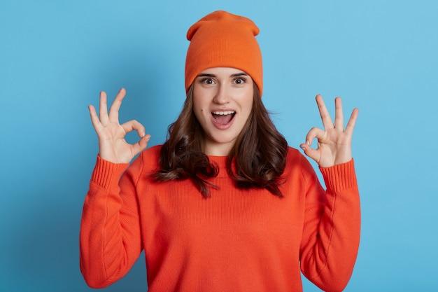 Jonge opgewonden vrouw die oranje sweater en pet draagt die camera met geopende mond bekijkt en ok tekens met beide handen toont, donkerharig meisje dat over blauwe muur wordt geïsoleerd.