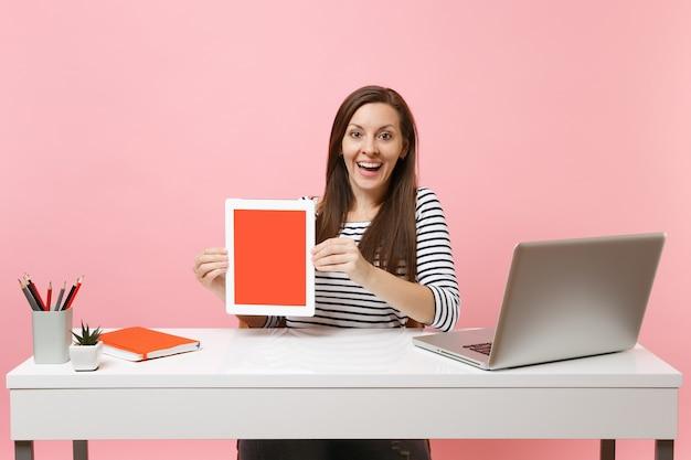 Jonge opgewonden vrouw houdt tabletcomputer vast met een leeg leeg scherm en zit aan het werk aan een wit bureau met een moderne pc-laptop