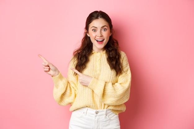 Jonge opgewonden vrouw in vrijetijdskleding, met banner, wijzende vingers opzij gelaten kopie ruimte, staande tegen roze muur.
