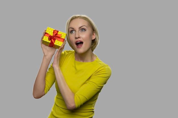 Jonge opgewonden vrouw schudden geschenkdoos. vrij vrolijke vrouw die aan giftdoos luistert tegen grijze achtergrond. ruimte voor tekst.