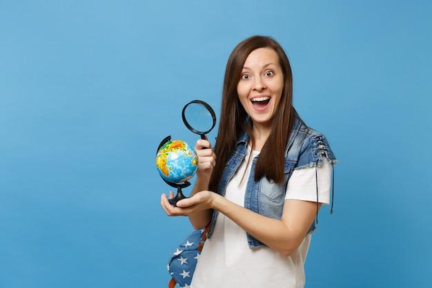 Jonge opgewonden vrouw student in denim kleding met rugzak op zoek op wereldbol met vergrootglas leren over landen geïsoleerd op blauwe achtergrond. onderwijs in middelbare school hogeschool.
