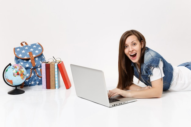 Jonge opgewonden vrouw student in denim kleding werken op laptop pc computer liggend in de buurt van globe, rugzak, schoolboeken geïsoleerd