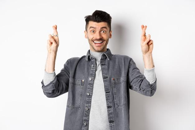 Jonge optimistische man die hoopt op een droom die uitkomt, wens doet met gekruiste vingers, lachend en verwacht goed nieuws, staande op een witte achtergrond.