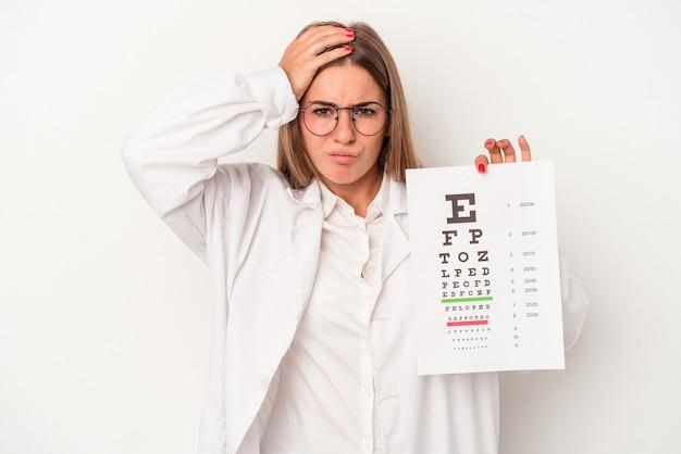 Jonge optometrist russische vrouw geïsoleerd op een witte achtergrond geschokt, ze heeft belangrijke vergadering herinnerd.