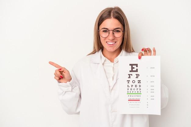 Jonge optometrist russische vrouw geïsoleerd op een witte achtergrond glimlachend en opzij wijzend, iets tonen op lege ruimte.