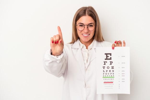 Jonge optometrist russische vrouw geïsoleerd op een witte achtergrond met nummer één met vinger.