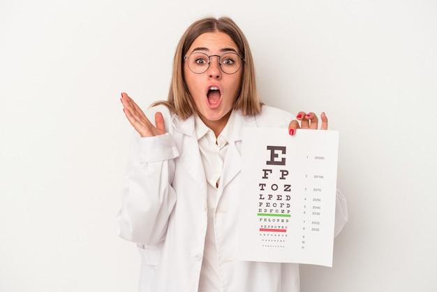 Jonge optometrist russische vrouw geïsoleerd op een witte achtergrond verrast en geschokt.