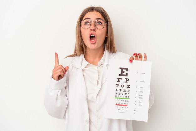 Jonge optometrist russische vrouw geïsoleerd op een witte achtergrond wijzend ondersteboven met geopende mond.