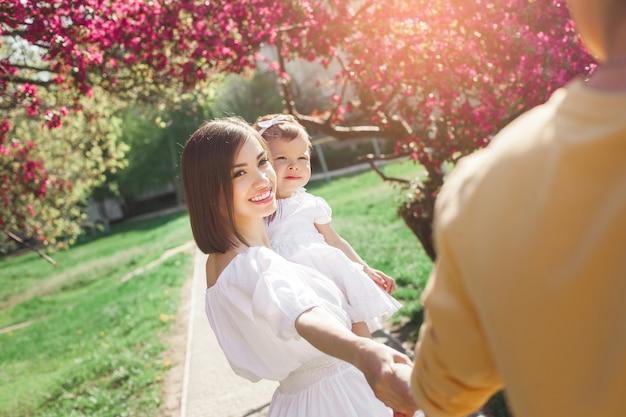 Jonge ouders die hun dochtertje houden. gelukkige familie buiten. moeder, vader en schattige baby plezier.