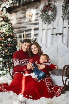 Jonge ouders en de babyjongen hebben samen plezier in het interieur dat is versierd voor kerstmis.