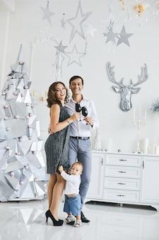 Jonge ouders en hun peuterzoon vieren nieuwjaar. jonge vrouw en knappe man poseren met hun schattige zoontje in het interieur versierd voor kerstmis