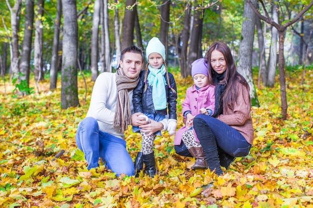 Jonge ouders en twee kinderen in de herfstpark op een zonnige warme dag