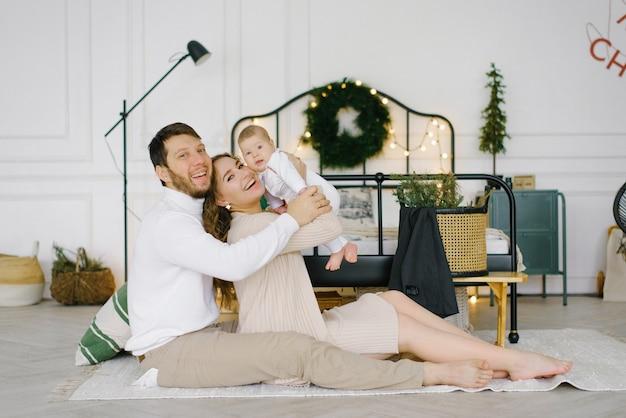 Jonge ouders heffen hun baby in hun armen en glimlachen naar hem
