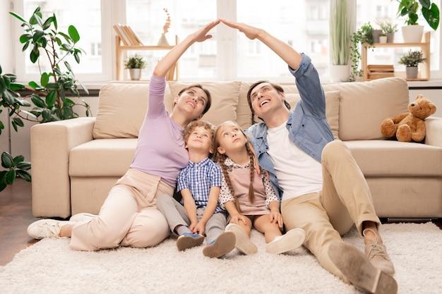 Jonge ouders houden hun handen dicht en vormen het dak boven hun twee kleine kinderen terwijl ze op de vloer van de woonkamer zitten