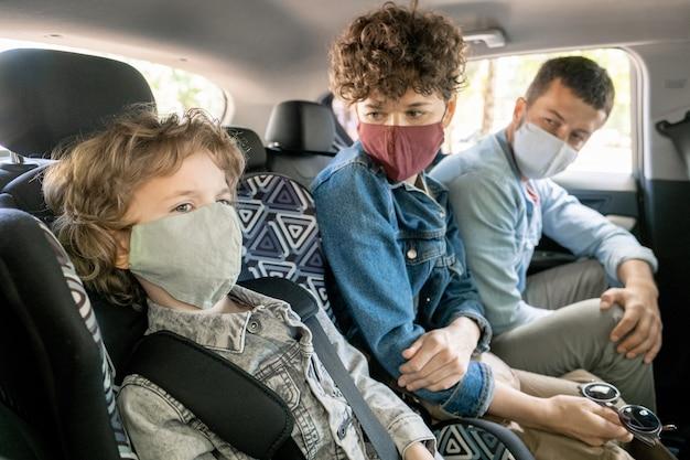 Jonge ouders in vrijetijdskleding en beschermende maskers kijken naar hun blonde krullende zoontje zittend op de achterbank van de auto en praten