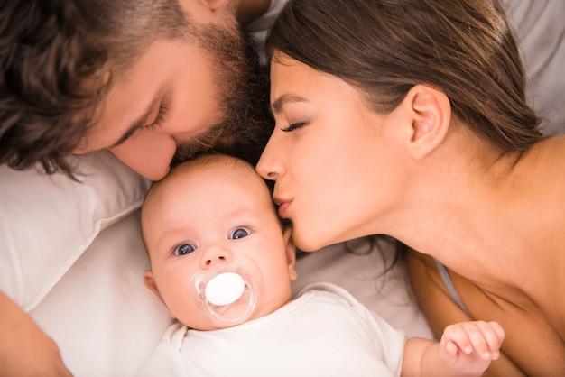 Jonge ouders met baby in het bed thuis.