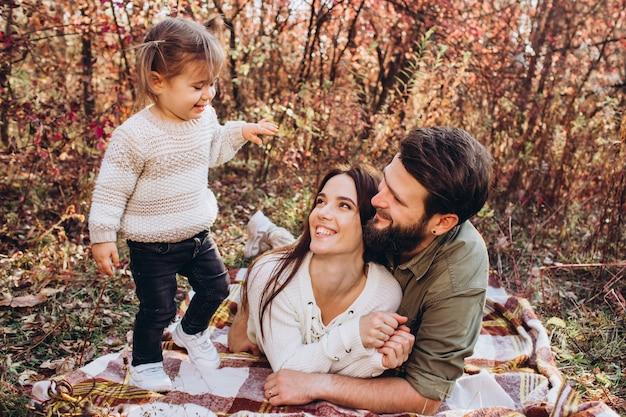 Jonge ouders met dochter lopen in herfst park