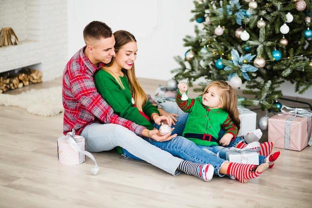 Jonge ouders met dochter naast kerstboom