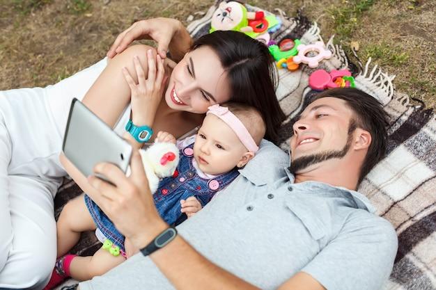 Jonge ouders met een klein kind hebben plezier en kijken een filmpje op een tablet