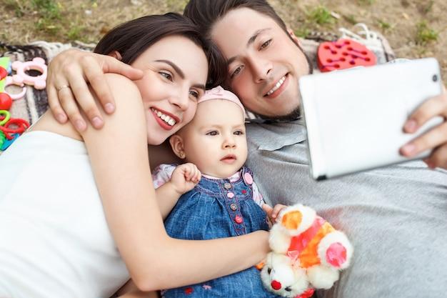 Jonge ouders met een klein kind hebben plezier en kijken naar een film op een tablet. geluk