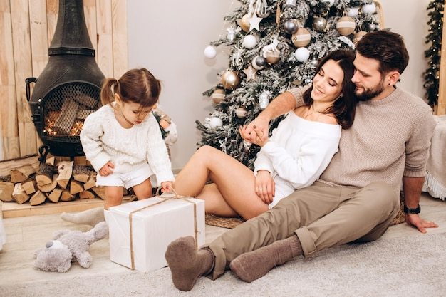 Jonge ouders met een kleine dochter in de buurt van de kerstboom