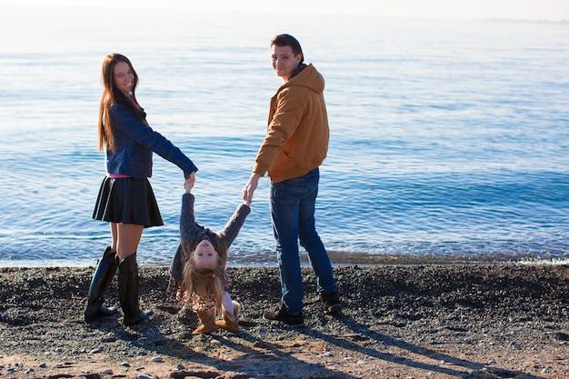 Jonge ouders met hun dochtertje in de buurt van de zwarte zee
