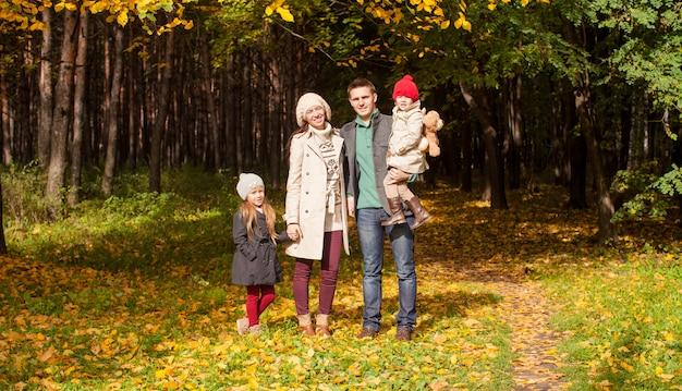 Jonge ouders met hun prachtige mooie dochter lopen in de herfstpark op een zonnige warme dag