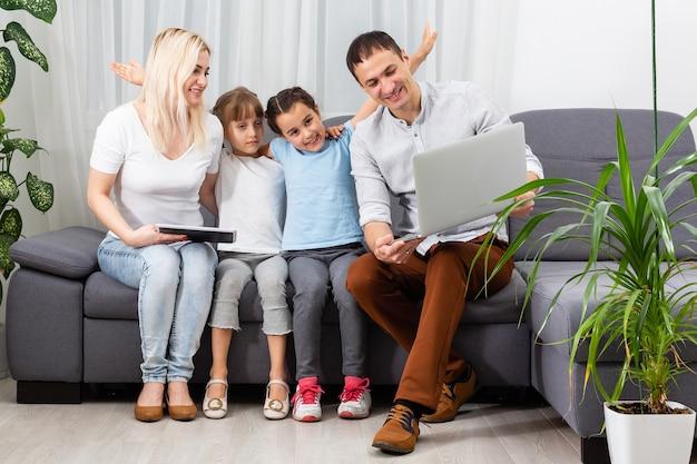 Jonge ouders, met kinderen, op laptopcomputer