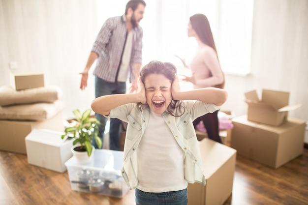 Jonge ouders vechten met elkaar en maken ruzie. ze zijn boos op elkaar. hun dochter is daarom niet blij. ze heeft haar oren met handen gesloten en schreeuwend.