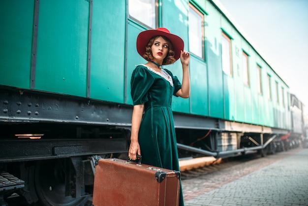 Jonge ouderwetse vrouw reist op retro trein. oude locomotief. spoorwegplatform, treinreis