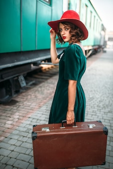 Jonge ouderwetse vrouw reist op retro trein