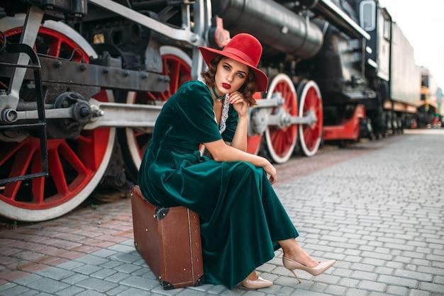 Jonge ouderwetse vrouwenzitting op koffer tegen uitstekende stoomtrein, rode wielenclose-up. oude locomotief. spoorwegmotor, reizen per spoor